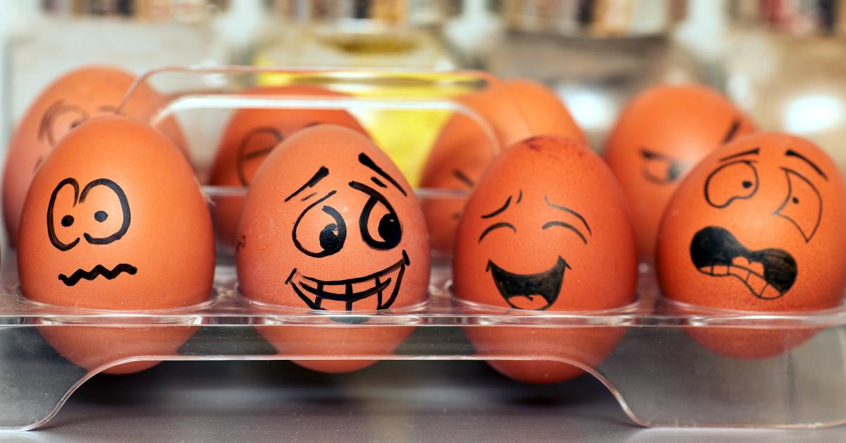 Mit schwarzem Filzstift bemalte Eier in einem Eierfach, darauf Gesichter mit verschiedenen Emotionen.